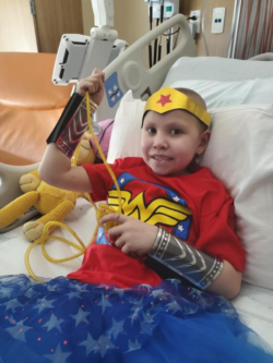 Cienna wearing Wonder Woman tshirt and headband while in hospital bed