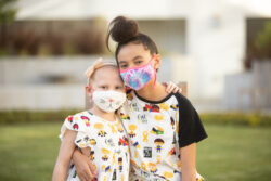 Cienna battles cancer and poses with her sister, both wearing masks