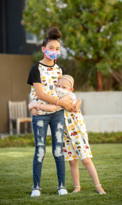 Cienna battles cancer and poses with her sister, both wearing masks and hugging eachother