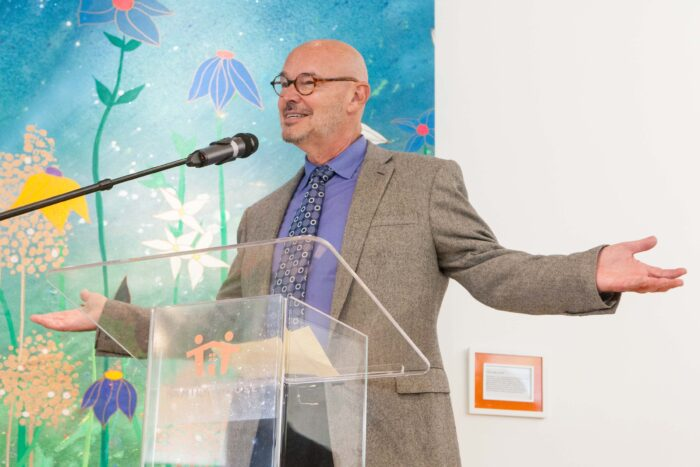 Picture of philanthropist Stephen Grand, bald and wearing glasses in blue tie and collared shirt with grey sportcoat, arms open and speaking into a microphone at the grand opening of the Nancy and Stephen Grand Family House in San Francisco's Mission Bay