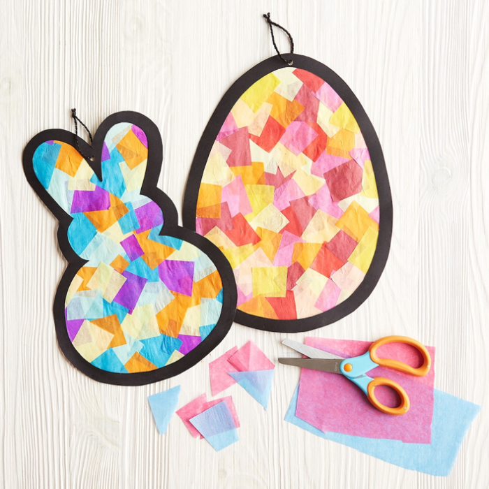 picture of a craft project with an outline of a bunny and an egg filled with squares to look like stained glass; scissors and colored tissue paper are to the side of the image